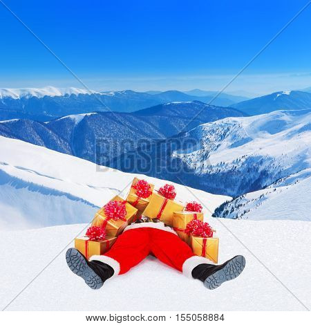 Funny Santa Claus spread out legs heap up with many Christmas golden gift boxes wrapped with red bows for children lying on snow against winter mountain landscape and blue skyNew Year holiday concept