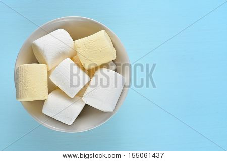 Marshmallow in bowl on blue table top view