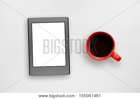 Electronic book and coffee cup on white table