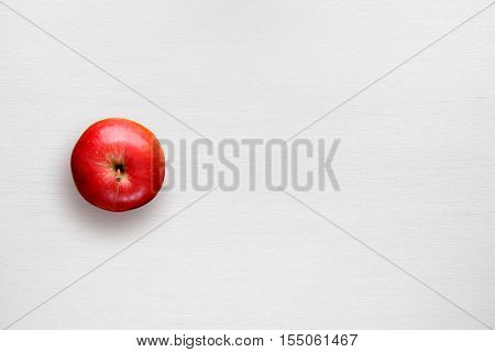 Red apple on white table top view