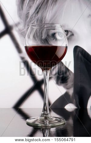 Red wine glass against black and white girl poster. Sight through the glass. Noir style concept