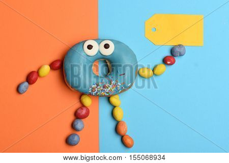 Blue funny surprised glazed donut with icing or sprinkles colorful dragee with raisins or peanuts inside and yellow tag on colorful background