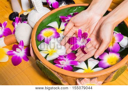 Woman Hands With A Bowl Of Aroma Spa Water On Wooden Table
