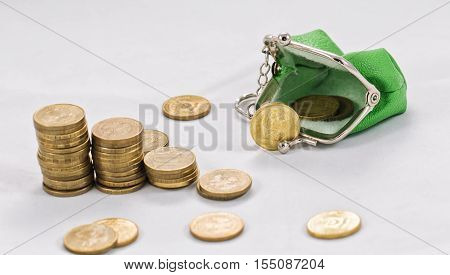 Gold plated coins are in stacks to increase against the background of a simple purse with coins