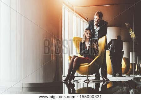 Businesswoman in red dress and jacket on yellow armchair showing information on screen of her tablet to her thoughtful boss in formal suit with white laptop, luxury office interior with a lot of reflections