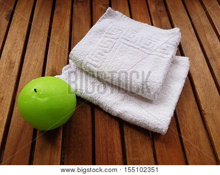 Set bath: Terry white towels and a round green candle. All this on wooden boards