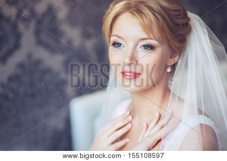 Beautiful young bride with wedding makeup and hairstyle in bedroom.Beautiful bride portrait with veil over her face. Closeup portrait of young gorgeous bride. Wedding.