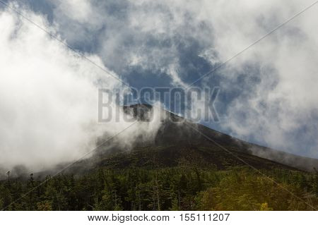 Mount Fuji Japan - September 27 2016: Dark Mount Fuji summit under white clouds as seen from Walk-up Station Five. Forests in foreground.