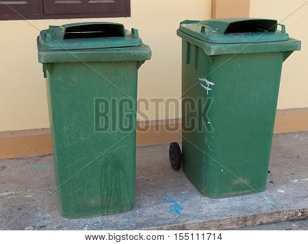 dustbins outside against cement wall Garbage disposal.