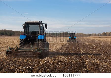 The sloping field. Two large blue traktor plow plowed land after harvesting the maize crop on a sunny clear autumn day.