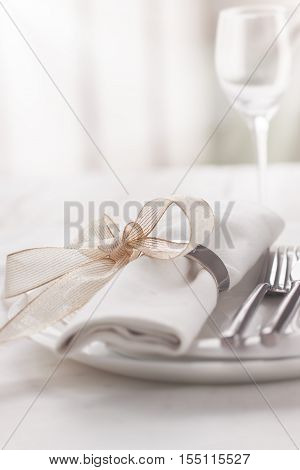 Beautifully elegant decorated table for holiday - wedding or valentine day with modern cutlery bow glass candle and gift closeup toned