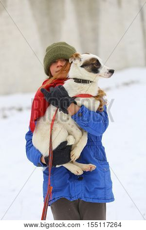 Young woman with her dog on the snow in winter.Girl hugging dog.Woman outdoors with her cute dog having fun.