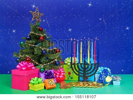 Christmas tree with presents next to Hanukkah menorah burning candles dreidel chocolate gold coin gifts. Many multi faith families celebrate both Xmas and Hanukkah. This year they are both Dec 25