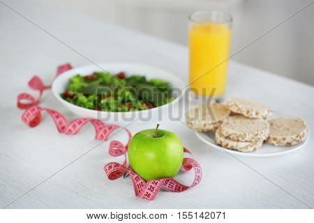 Measuring tape with green apple and vegetable salad on table