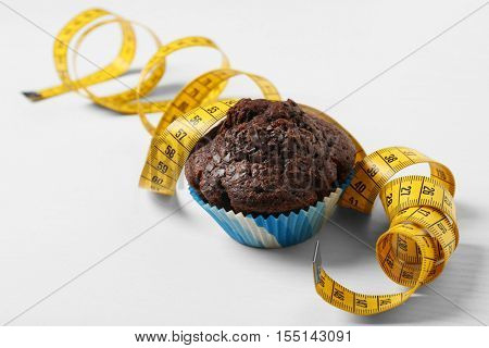 Chocolate muffin with centimeter on white background