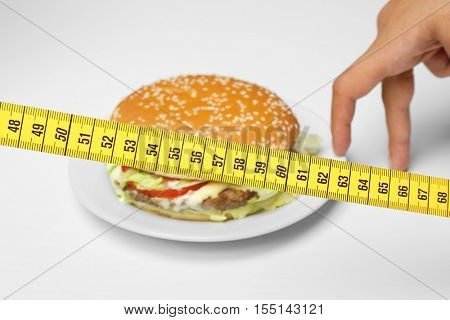 Centimeter, hamburger on white plate and female hand