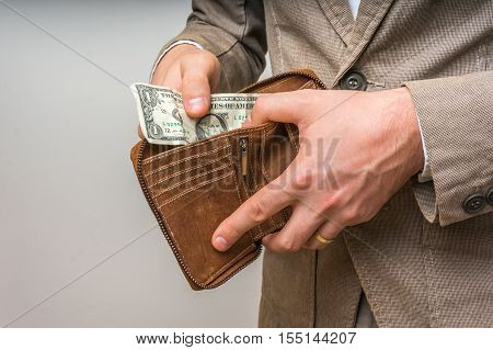 Man Holding Wallet With Only One Dollar Inside