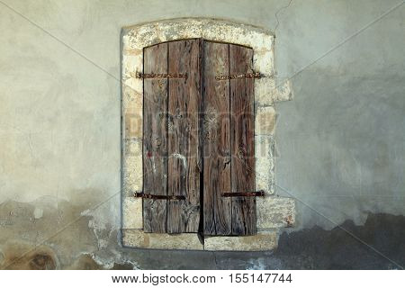 antique wooden shutters window in old stone house