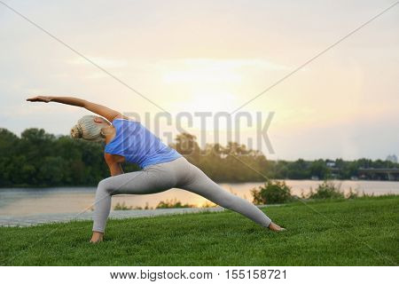 Young beautiful woman practicing yoga on grass near pond