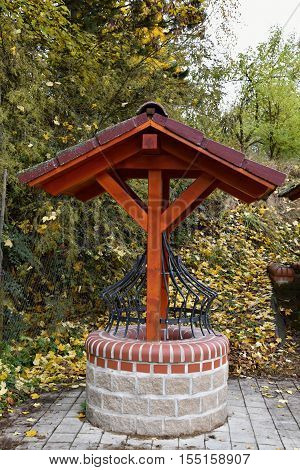 Ornamental well with the shelter in the autumn. Well.