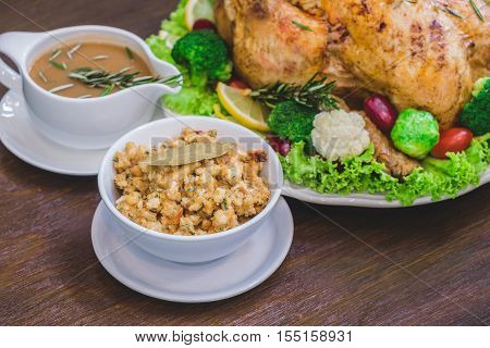 Close up of Thanksgiving turkey stuffing made with bread and herb on a wooden table.