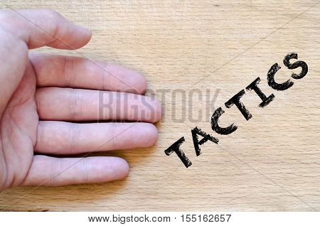 Human hand over wooden background and tactics text concept