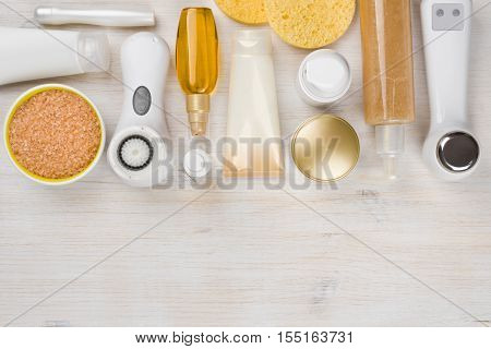 Beauty treatment products on wooden background with copyspace at bottom