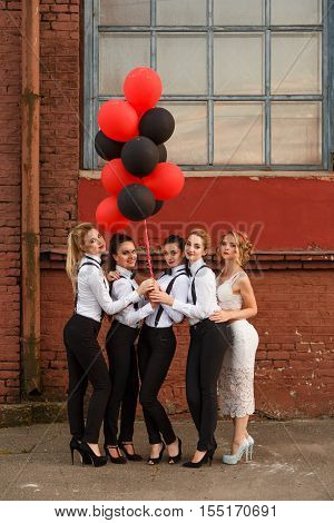 Cute young women wearing dress code celebrating hen-party with balloons