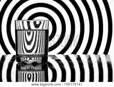 glass of water on a background of black and white geometric shapes
