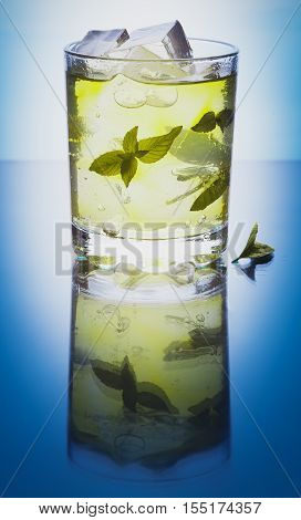 Mojito cocktail with mint and ice in glass on the blue background