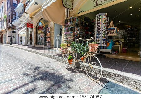 Rethymnon, Island Crete, Greece - July 1 2016: The tourist shop on the street of the old town of Rethymnon and the bicycle with flowers.