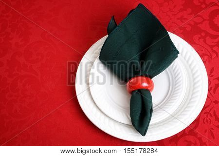 christmas place setting with green napkin on red tablecloth