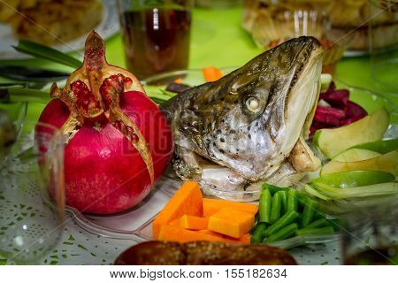 Rosh Hashanah traditional dish with the fish head pomegranate fruits and vegetables for Jewish New Year