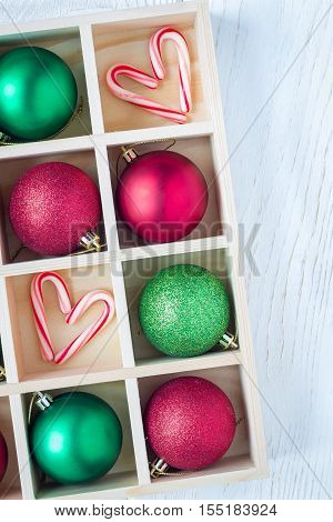 Preparation for Christmas: festive balls and candy cane in wooden box on white wooden table vertical copy space