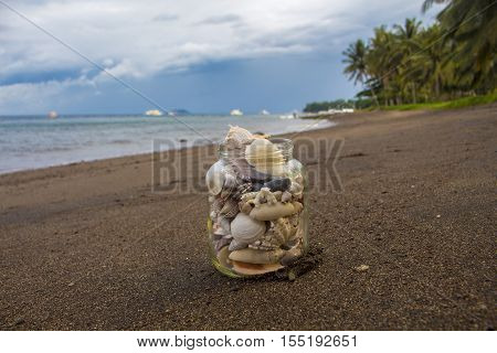 Seashells in glass on the sand beach. Cloudy sky evening. Tropical landscape with sea, white boats, coco palm trees. Shells collection from the seashore on seascape background. Vacation memories