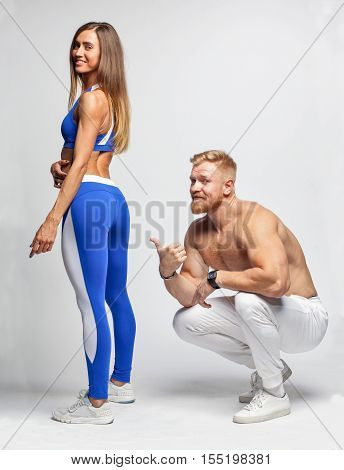 Man Trainer Showing Muscular Butt Of Sexy Woman