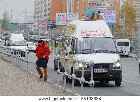 BALASHIKHA RUSSIA - OCTOBER 28: Passengers exiting the taxi on Sverdlov Street on October 28 2016 in Balashikha. Balashikha is city in Moscow Oblast Russia located on Pekhorka River 1 kilometer east of Moscow.