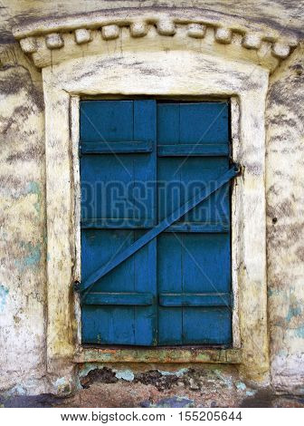 Old window with blue shutters closed in the old stone house.