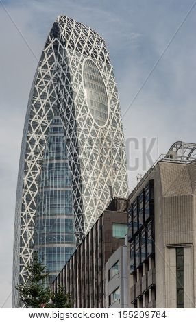 Tokyo Japan - September 28 2016: The glass-and-iron iconic Cocoon-shaped tower or Tokyo Mode Gakuen peeks over other buildings under light blue sky.
