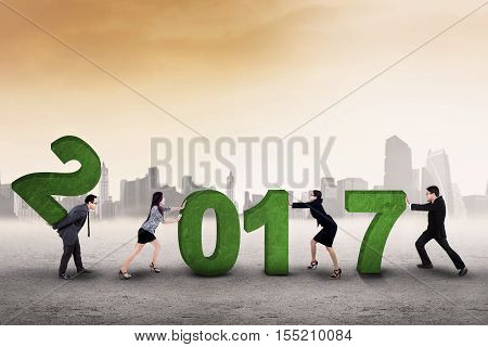 Image of business team trying to arrange number 2017 symbolizing of working together for the future