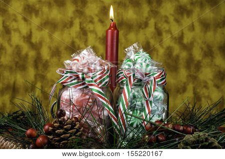 glass jars full of red and green Christmas candy burning candle and holiday pine garland