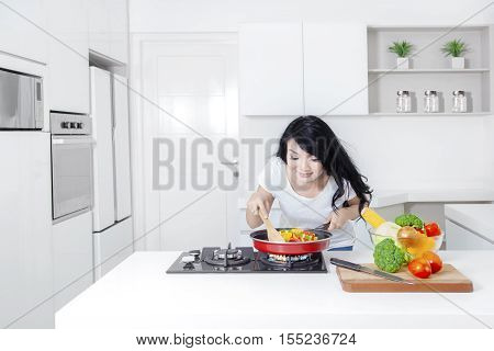 Picture of a pretty Asian woman cooking in the kitchen and sniff meal on the frying pan shot at home