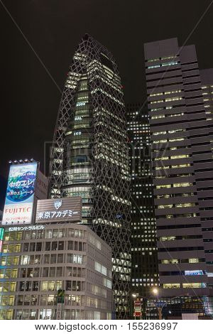 Tokyo Japan - September 29 2016: Night photo of the cocoon building the Tokyo Mode Gakuen adjacent to L-building. Plenty of lights and a few large neon signs.