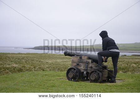Girl shooting cannon at Orkney coastline cliff landscape