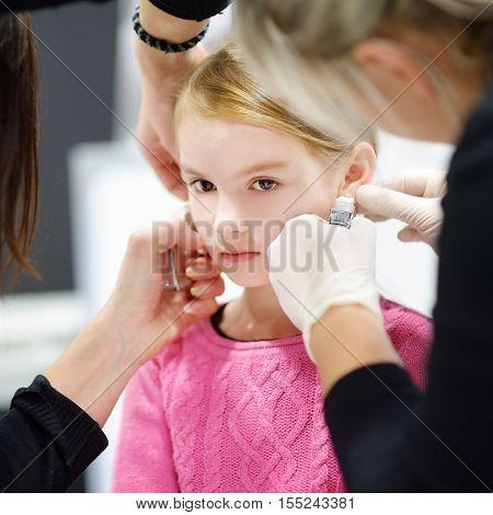 Adorable Little Girl Having Ear Piercing Process In Beauty Center