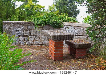 Stone arbor consisting of table and a bench silent place anyone can relax in. San Marino Italy.