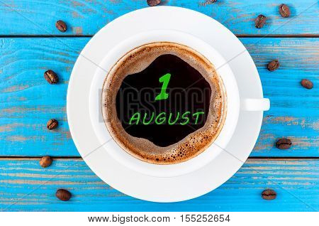 August 1st. Day of the month 1, morning coffee cup with calendar on drinks surface. Blue wooden background and beans. Top view. Summer time.