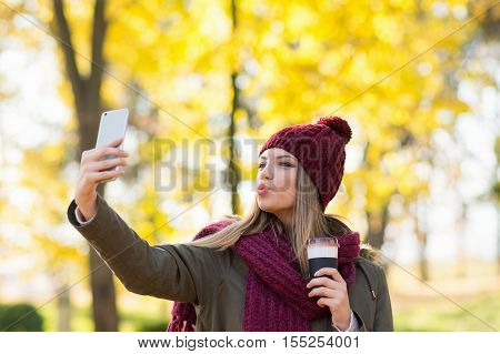 Young woman with takeaway coffee taking a selfie on smart phone in park in autumn. Millennial teenage girl in fall taking a photo of herself using cellphone. Vibrant colors, natural light.