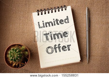 Text Limited time offer on white paper book and office supplies on blue desk / business concept