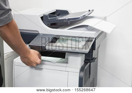 close up businessman take a business documents from printer